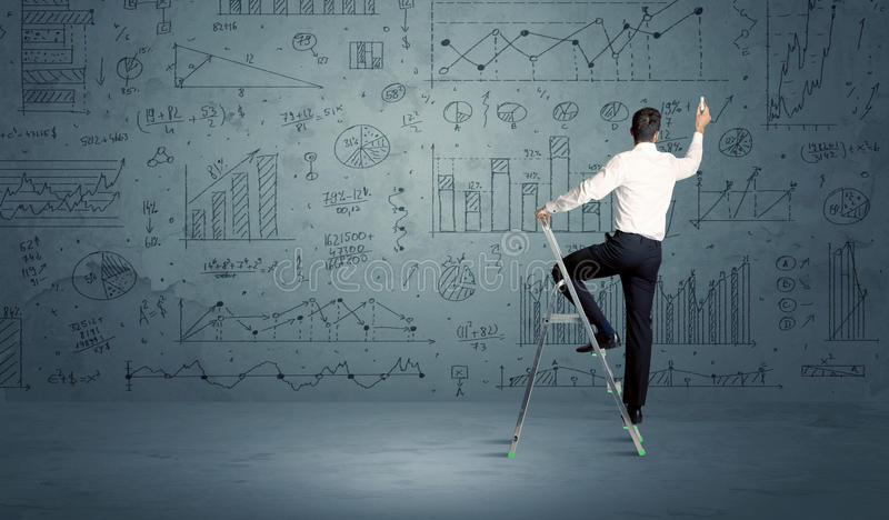 Man on ladder drawing charts. A businessman in modern stylish elegant suit standing on a small ladder and drawing pie and block charts on grey wall background royalty free stock images