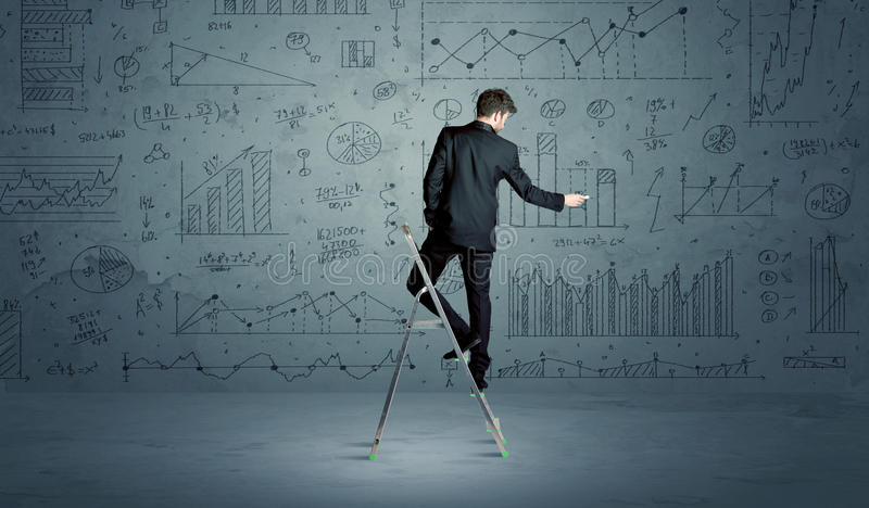 Man on ladder drawing charts. A businessman in modern stylish elegant suit standing on a small ladder and drawing pie and block charts on grey wall background stock photo