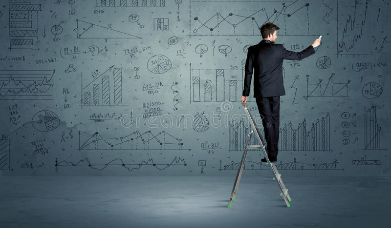 Man on ladder drawing charts. A businessman in modern stylish elegant suit standing on a small ladder and drawing pie and block charts on grey wall background royalty free stock image