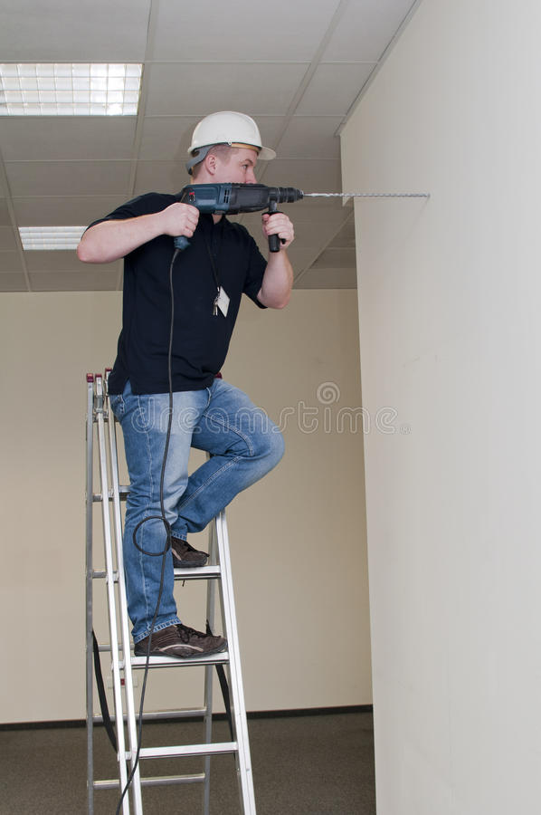 Man on a ladder drills drill stock image