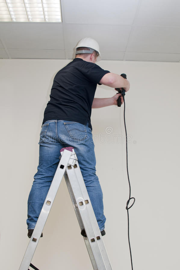 Man on a ladder drills drill royalty free stock images