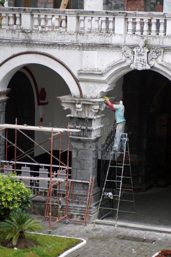 Man on a ladder. Making repairs in the courtyard of a church in Banos, Ecuador stock photo