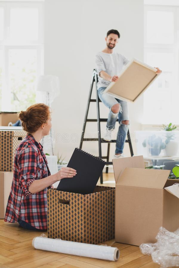 Man on ladder with painting and woman packing stuff into boxes while moving-out. Man on ladder with painting and women packing stuff into boxes while moving-out stock photography