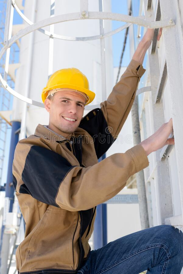 Man ladder poised to climb enclosed ladder stock photography