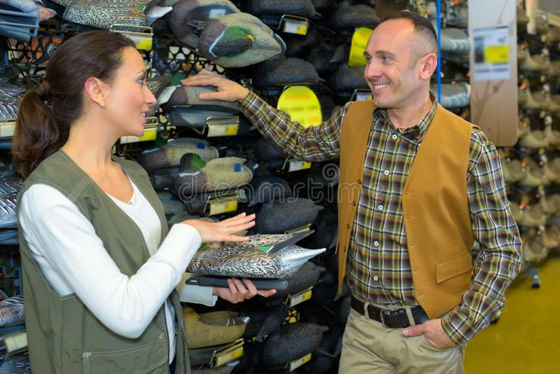 Man and lady in hunting shop. Hunter stock photography