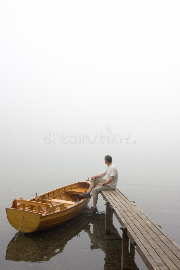 Man at a lake on misty morning stock images