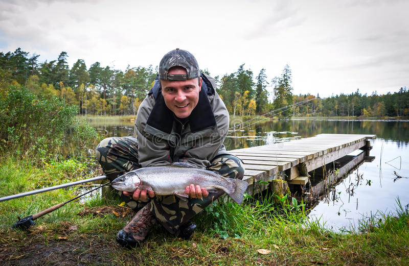 Man with lake rainbow trout. Autumn scenery of lake trout fishing in Sweden stock photography