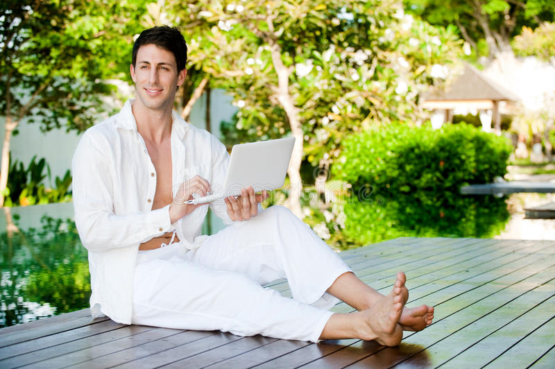 Man With Laptop. An attractive man lounging by the pool with his laptop outdoors stock photo