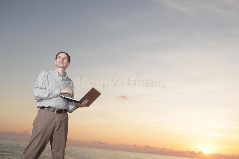 Man with laptop against sunset