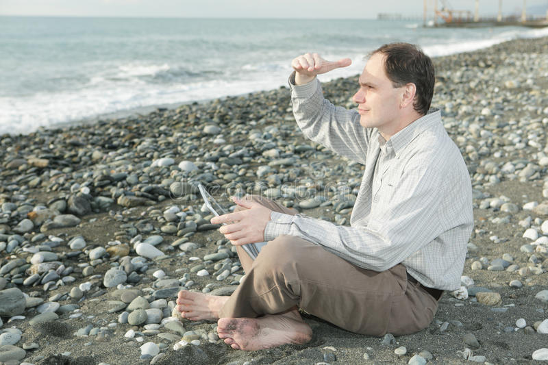 Man with laptop on the beach royalty free stock image