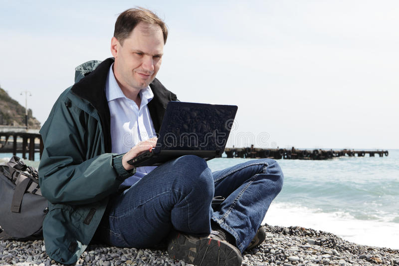 Man with laptop on beach stock photography