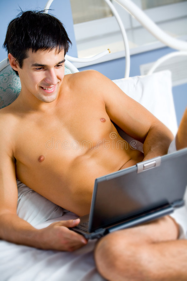 Man on laptop at bedroom royalty free stock images
