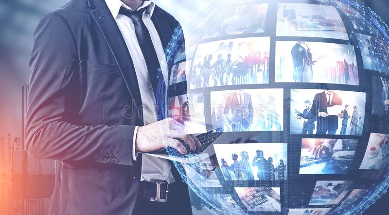 Man with laptop in city, streaming interface. Man using laptop in city with double exposure of futuristic video streaming interface. Concept of hi tech and royalty free stock image