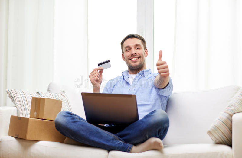 Man with laptop and credit card showing thumbs up. Technology, people and online shopping concept - smiling man with laptop computer, parcel boxes and credit royalty free stock photos