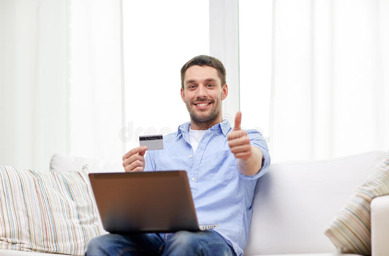 Man with laptop and credit card showing thumbs up. Technology, people and online shopping concept - smiling man with laptop and credit card at home showing royalty free stock photography