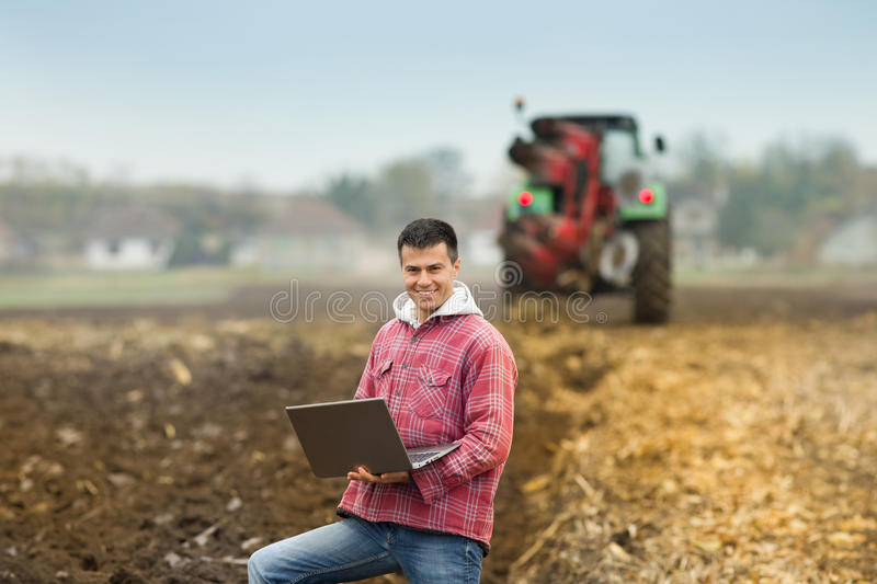 Man with laptop in the field. Young attractive peasant holding laptop in the field, tractor ploughing in the background royalty free stock photo
