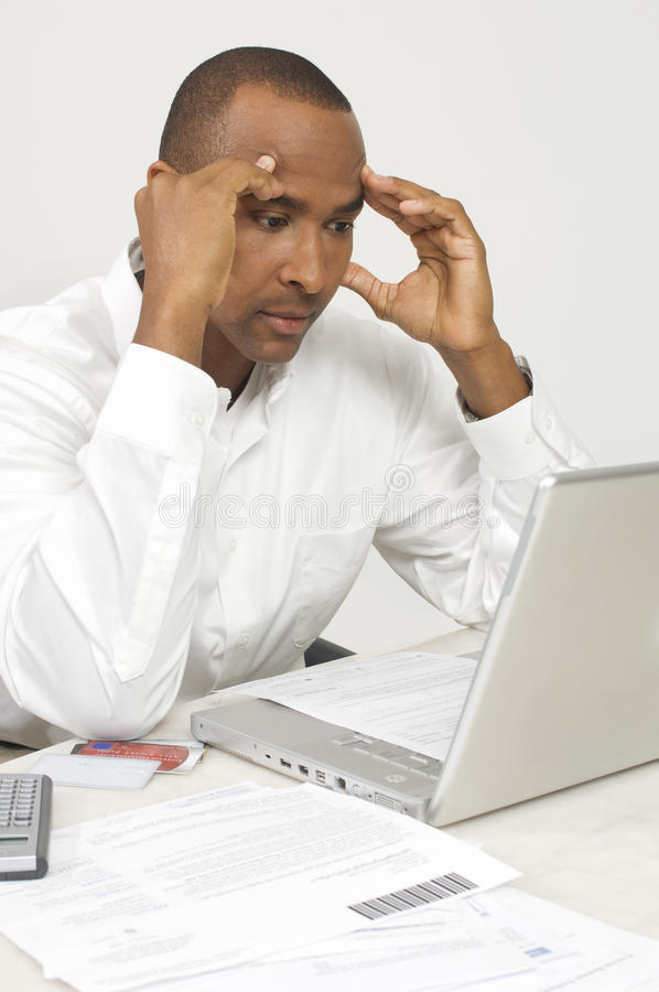 Man With Laptop Figuring Out Bills. Worried businessman with laptop figuring out bills stock photography