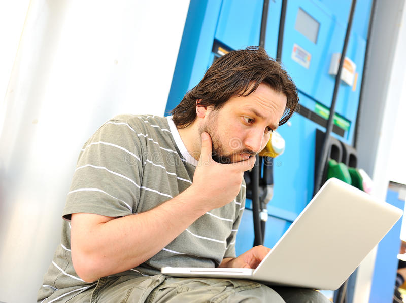Man with laptop on gas station. With silly expression on his face after reading last news stock photos
