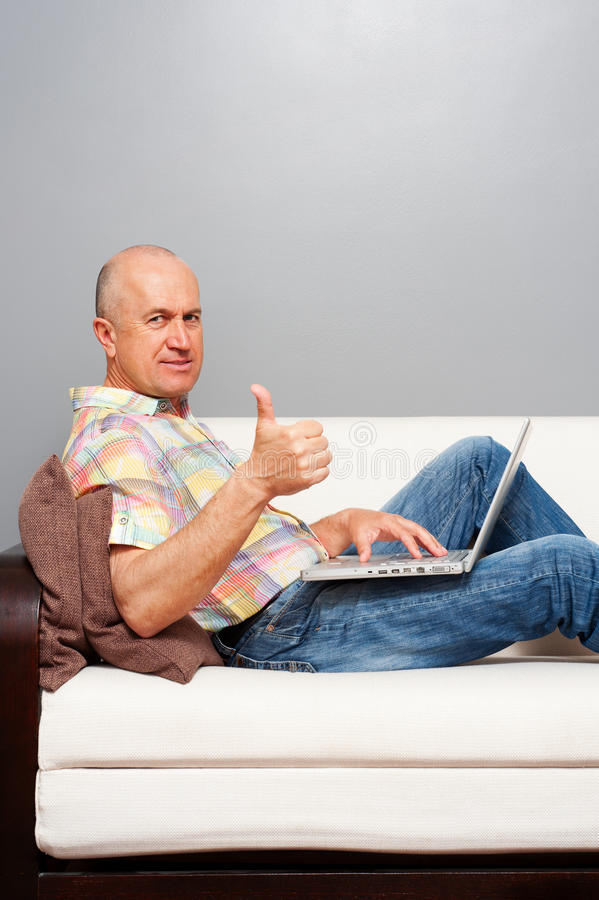 Man with laptop at home showing thumbs up. Senior man with laptop at home showing thumbs up stock photography