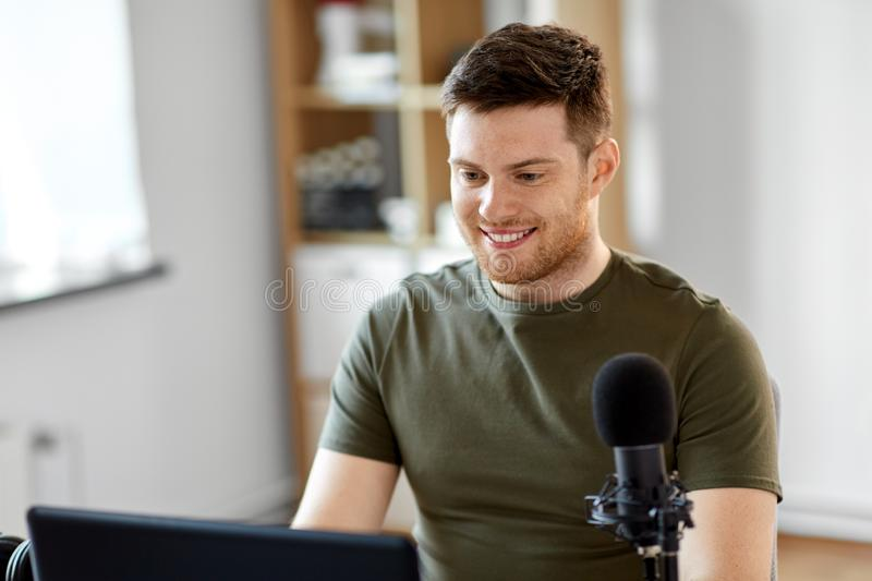 Man with laptop and microphone at home office royalty free stock photos