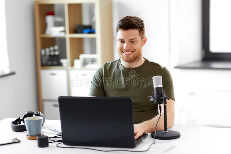 Man with laptop and microphone at home office stock photo