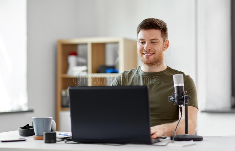 Man with laptop and microphone at home office royalty free stock images