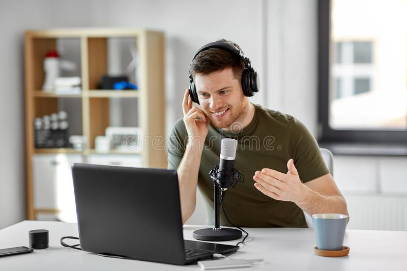 Man with laptop and microphone at home office stock image