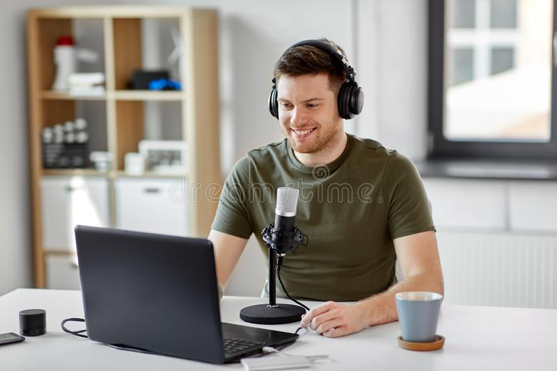 Man with laptop and microphone at home office royalty free stock image