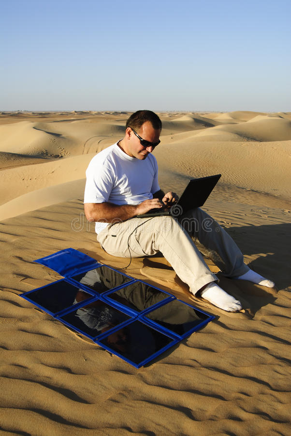 Man with laptop and portable solar charger royalty free stock image