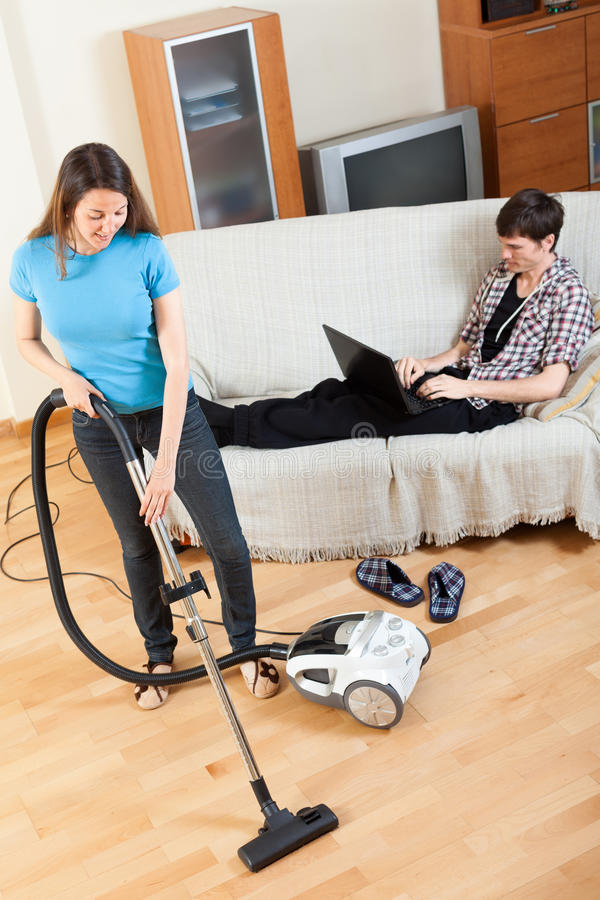 Man with laptop resting over sofa while girl doing house clean stock images