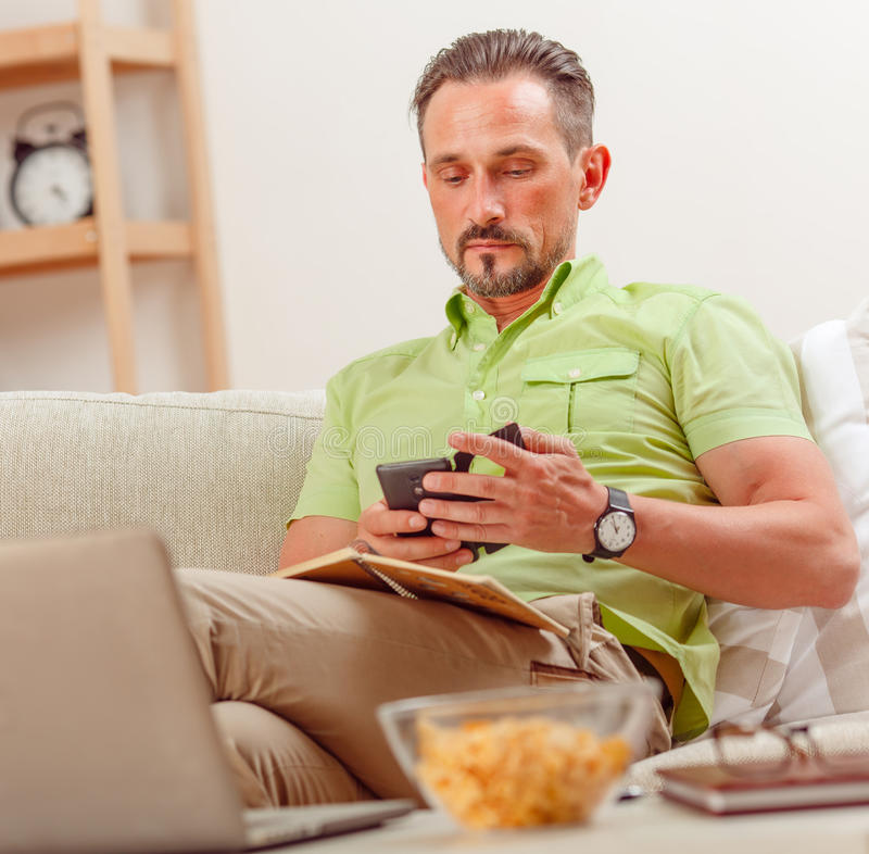 Man on laptop running business from home. Closeup portrait of businessman sitting on sofa and using mobile or smart phone for business purposes. Home business royalty free stock image