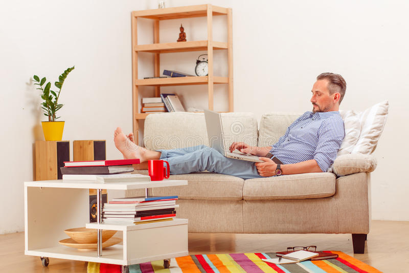 Man on laptop running business from home. Picture of handsome businessman lying on sofa and using laptop computer for business purposes. Man running business stock photo
