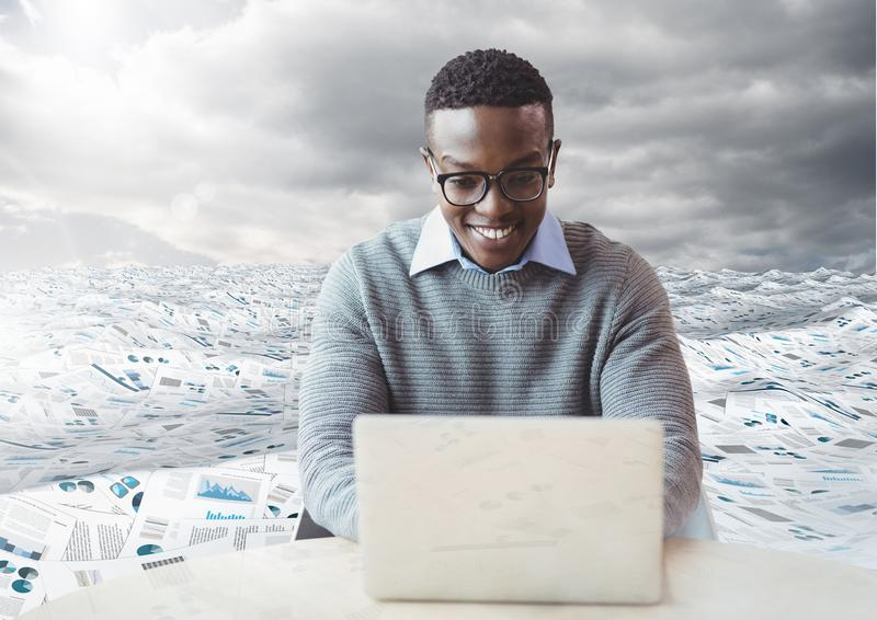man on laptop in sea of documents under sky clouds stock photography