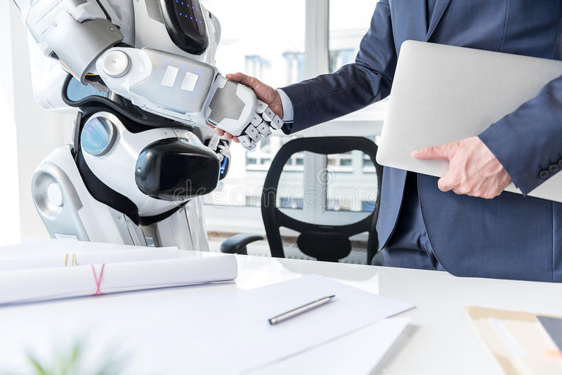 Man with laptop is shaking hands with android royalty free stock images
