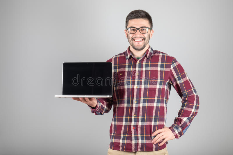 Man with laptop showing screeen. This is what you need! Confident young man carrying laptop and showing screeen of it standing against gray background stock photography