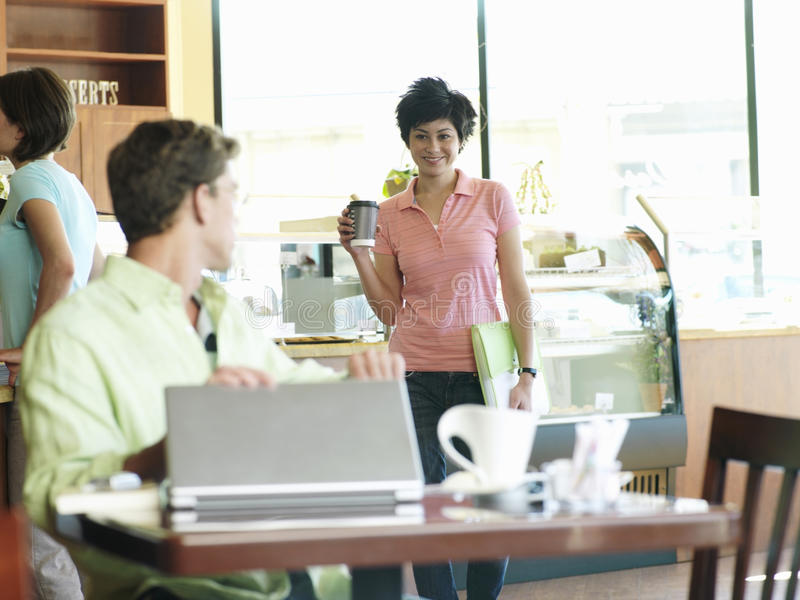Man with laptop sitting at cafe table, greeting young woman carrying mug of coffee, smiling royalty free stock photo