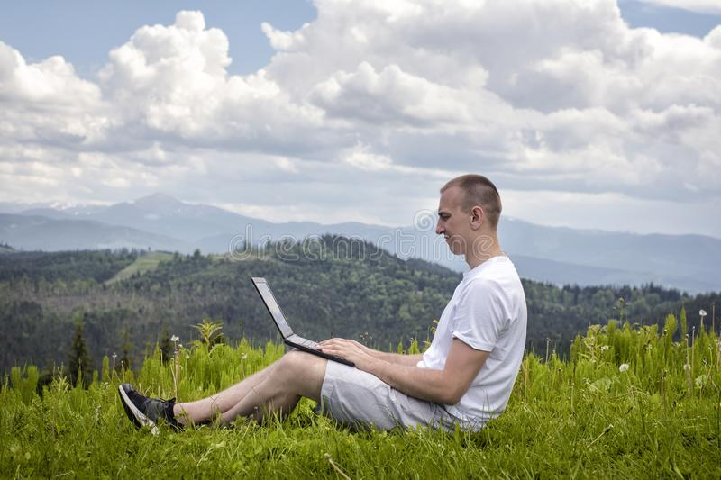 Man with laptop sitting on green grass on a background of mountains. Side view royalty free stock images