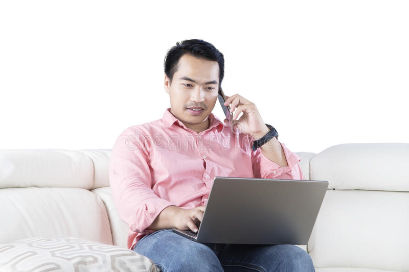 Man with laptop talking on smartphone royalty free stock photo