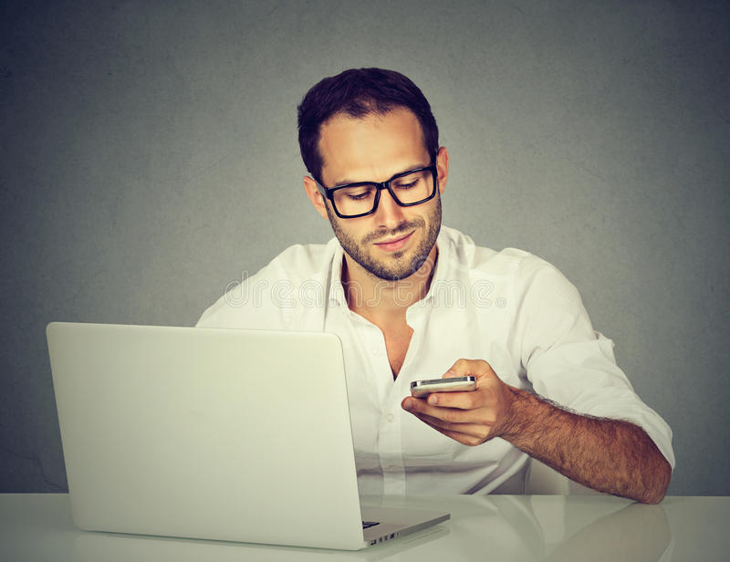 Man with laptop texting on mobile phone sitting at table stock images