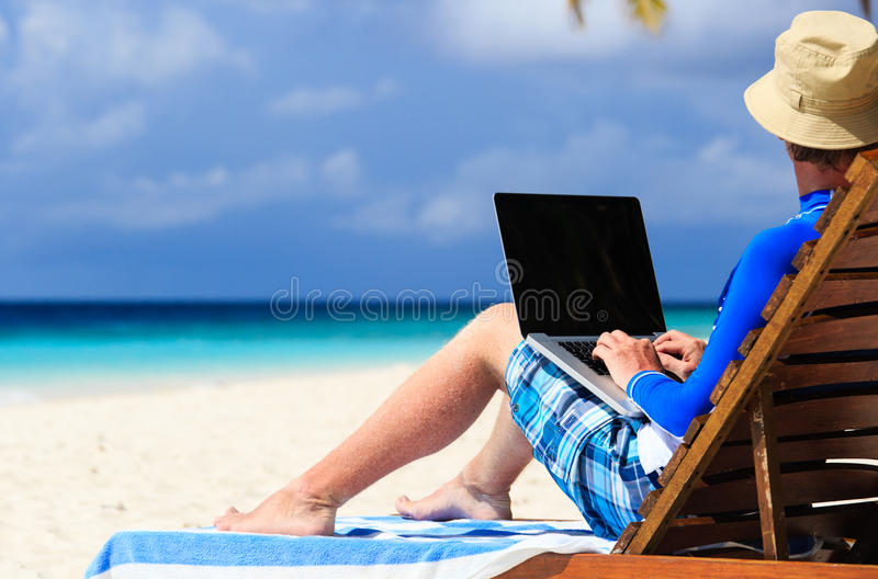 Man with laptop on tropical vacation stock image