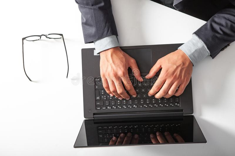 Man with laptop typing on the keyboard. On white table.. stock photography