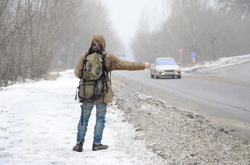 A man with a large backpack showing thumbs up for hitchhiking du. Ring road trip along a suburban asphalt road in a wintertime blizzard royalty free stock image