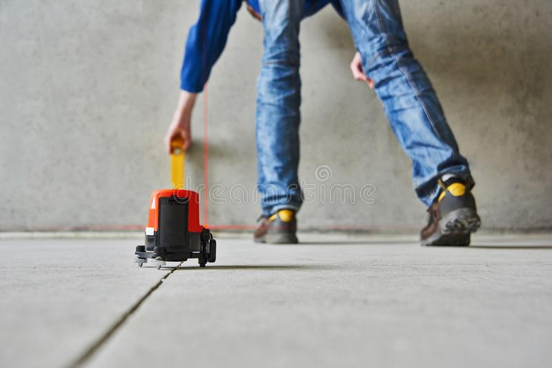 Man with laser level check floor and walls royalty free stock photo