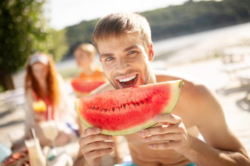Handsome man laughing while biting watermelon royalty free stock image
