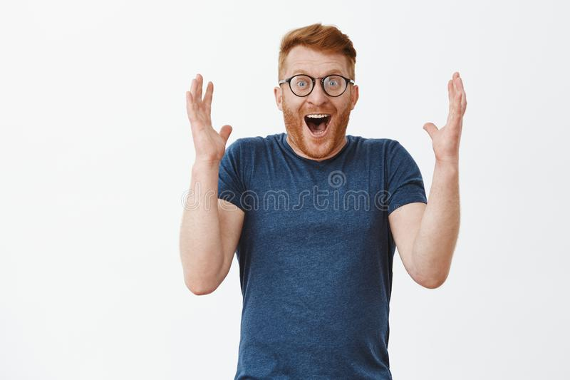 Man laughing joyfully from surprise and amazement, cannot believe he won lottery, raising palms high smiling broadly and. Chuckling, being happy and astonished royalty free stock image