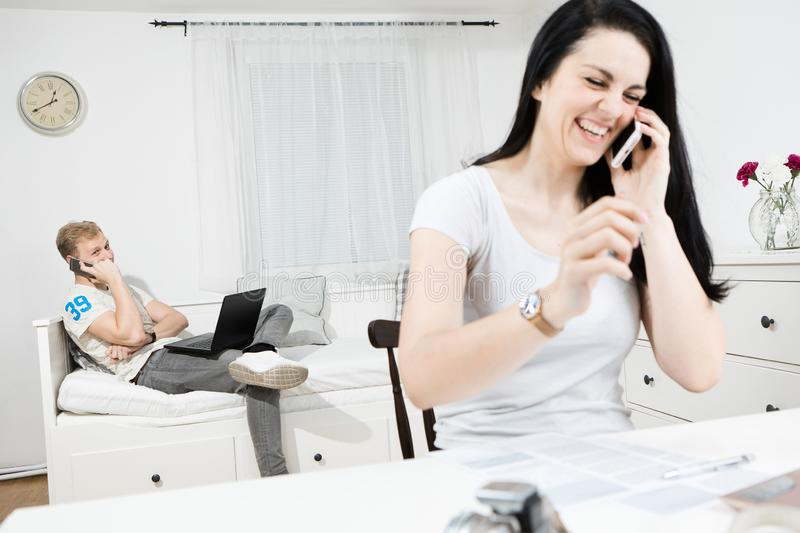 Man and laughing woman calling with cellphones stock photo