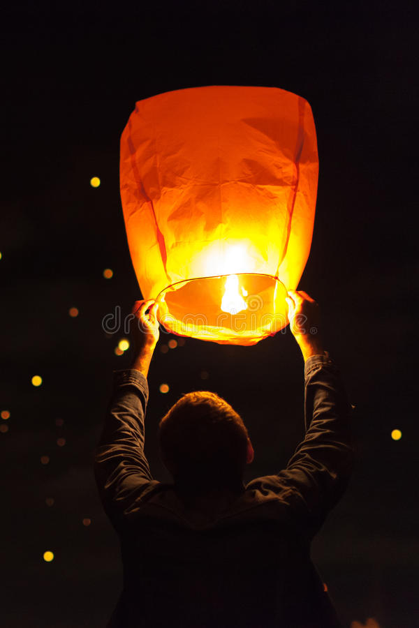 Man launches sky lanterns. Into the air stock image