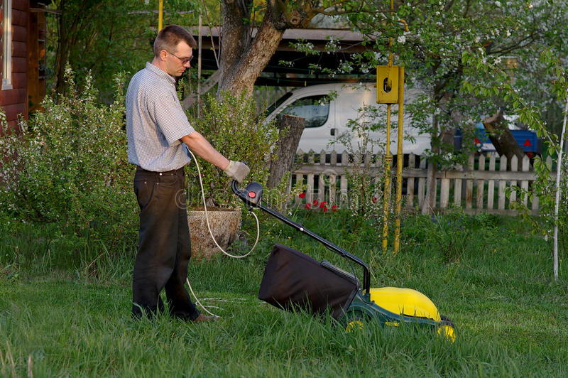 Man with the lawn mower royalty free stock photos