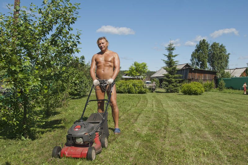 Man with the lawn mower. The young suntanned man (40 years) at a dacha mows in the summer a grass on a lawn royalty free stock photography
