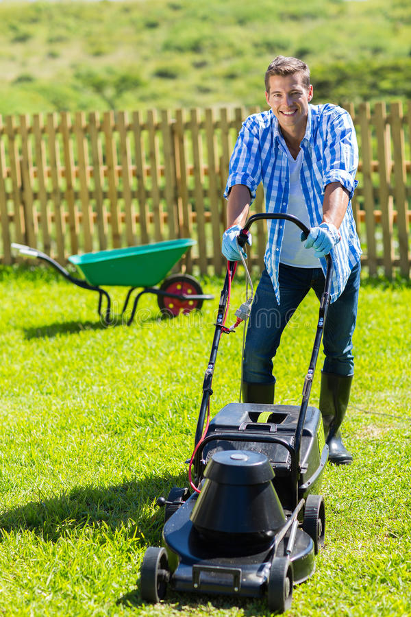 Man lawn mowing. Cheerful man lawn mowing in his home garden stock images